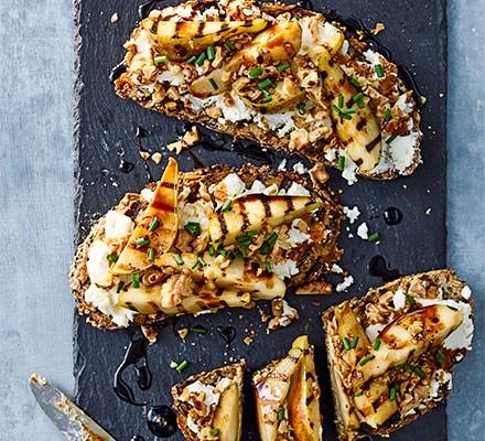Three goat's cheese, pear & walnut tartines on a serving platter