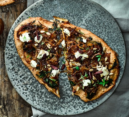 Goat's cheese and onion pizza sliced in half on a stone platter