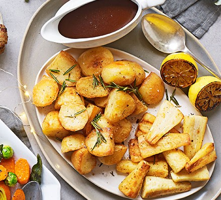 Golden goose fat potatoes & parsnips on a serving platter with baked lemons and a jug of gravy