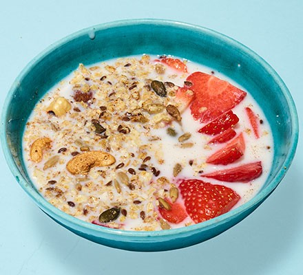 Low-sugar granola served with strawberries in a bowl