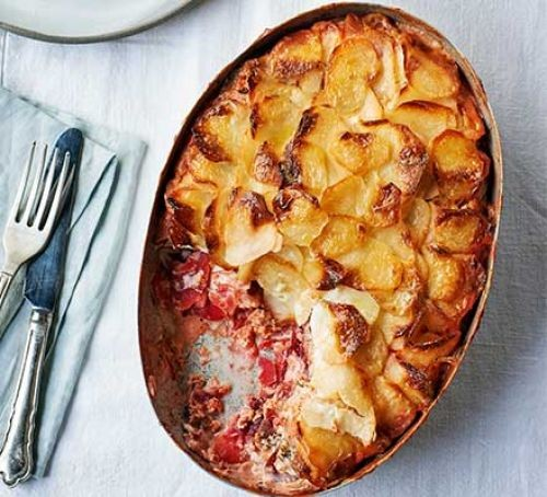 Potato and smoked salmon gratin in an oval dish with a portion taken out