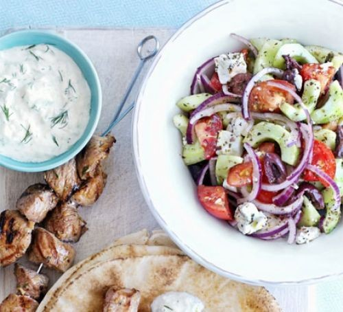 Bowl of Greek salad, with chicken skewers and tzatziki