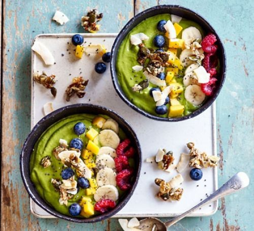 Two bowls of green smoothie topped with colourful fruit and nuts