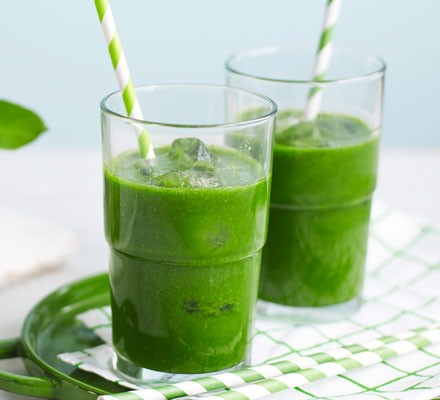 Green juice in glasses with ice and straws