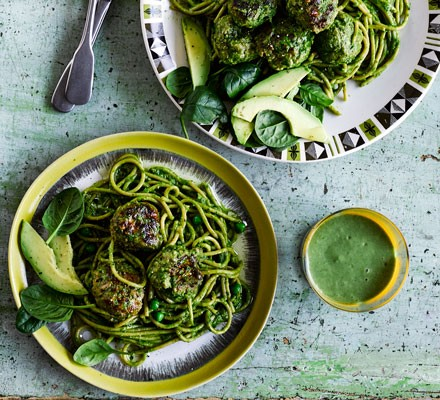 Green spaghetti with meatballs and avocado in bowls