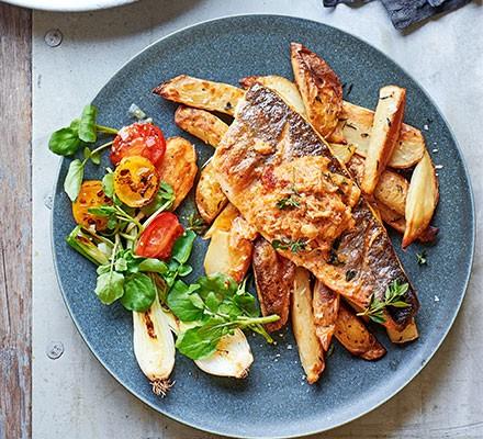 A plate serving grilled sea bass, crisp potato skins & crab butter