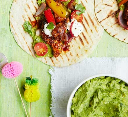A fajita with guacamole salsa served alongside