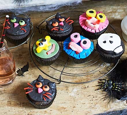 A range of Halloween cupcakes decorated with cat and monster designs