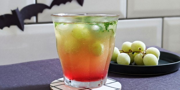 Cocktail in glass with frozen grapes