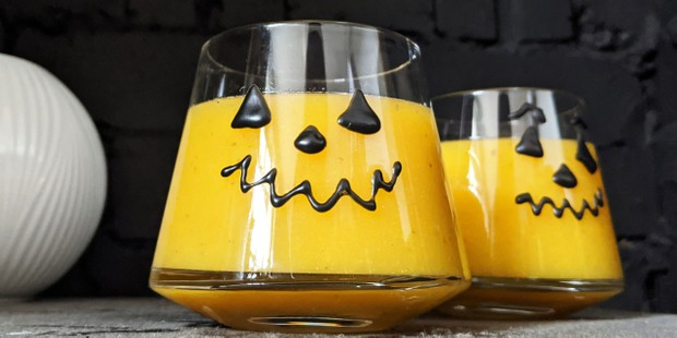 Pumpkin cocktail with face on glass