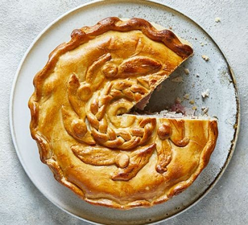 Ham and turkey shortcrust pastry pie with slice taken out