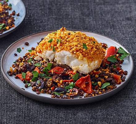 Harissa-crumbed fish with lentils, olives & peppers served on a plate