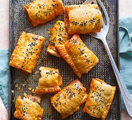 Harissa & lamb sausage rolls on a baking tray