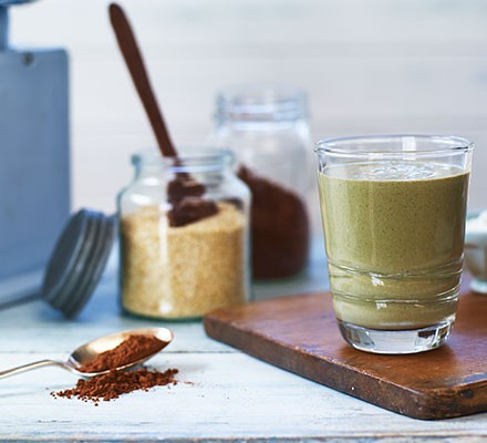 A glass of healthy chocolate milk on a wooden board with the ingredients alongside