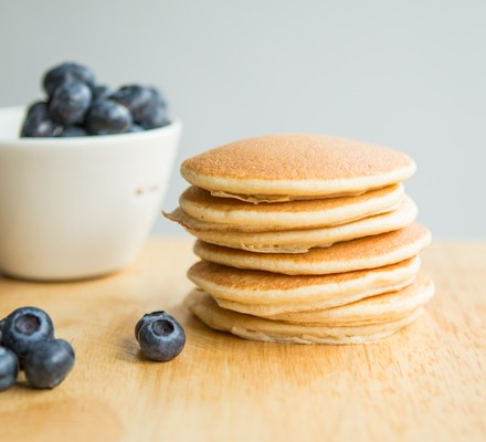 Stack of American pancakes on table with blueberries in bowl
