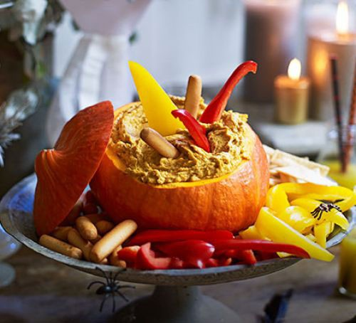 A hollowed-out pumpkin filled with healthy hummus and served with vegetable sticks
