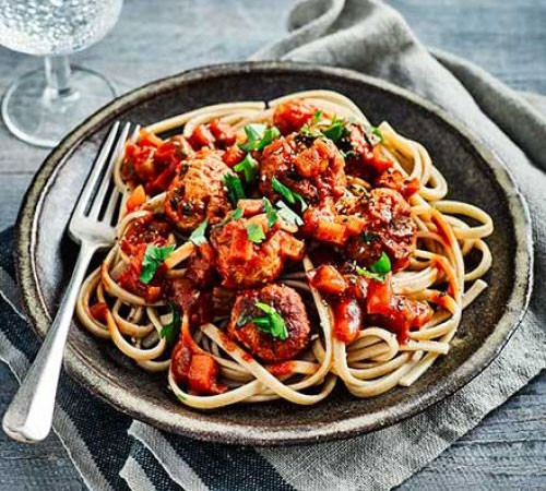 A bowl of spaghetti topped with slow cooker meatballs and sauce