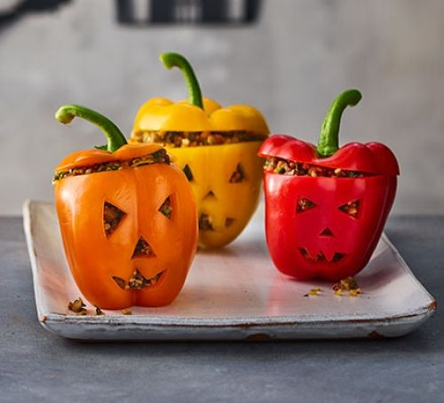 Three different coloured stuffed peppers peppers with scary carved faces