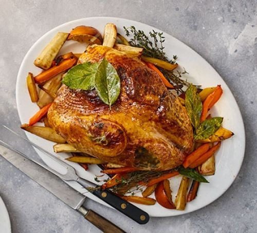 Roast turkey crown surrounded by root vegetables