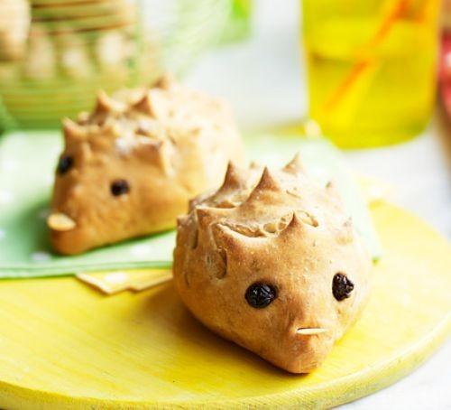 Two hedgehog-shaped bread rolls on a board