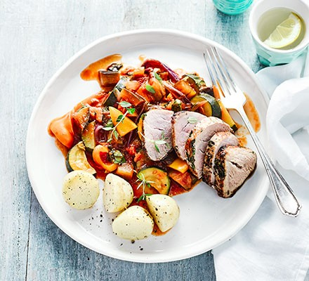 A plate with herb & garlic pork with summer ratatouille