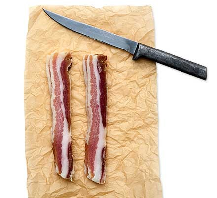 Two rashers of home-cured streaky bacon beside a knife