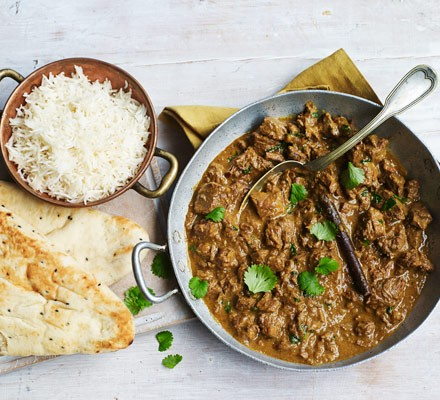 Beef curry in dish with spoon with rice and naan bread