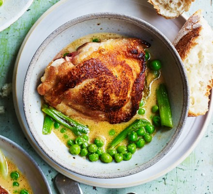 Chicken with peas and sauce in bowl with bread
