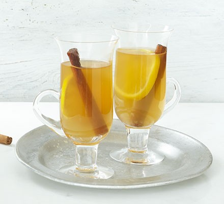 Two hot toddies in tall glasses on a silver serving dish
