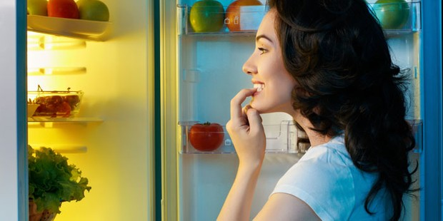 Woman looking in fridge and deciding what to eat