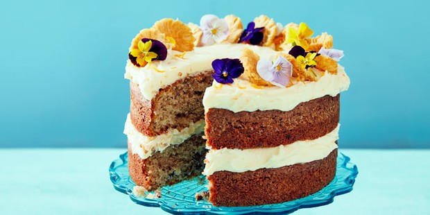 Multilayer hummingbird cake topped with icing and flowers