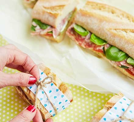 A filled baguette sliced into smaller sandwiches one of which is wrapped in baking parchment