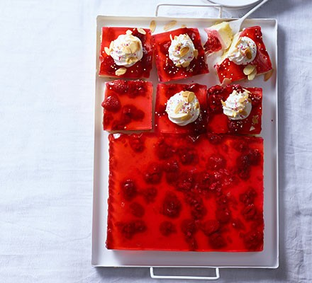 Jelly & custard trifle cut into squares in baking tin