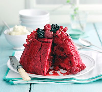 summer pudding with berries on blue table