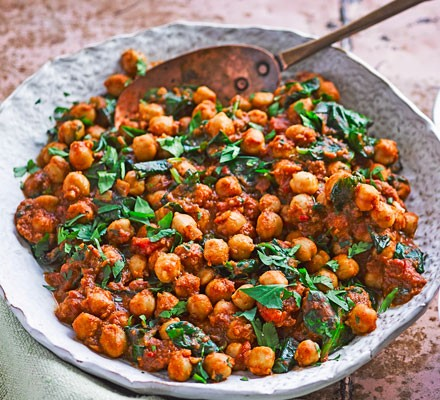 Chickpea curry in a round dish with spoon