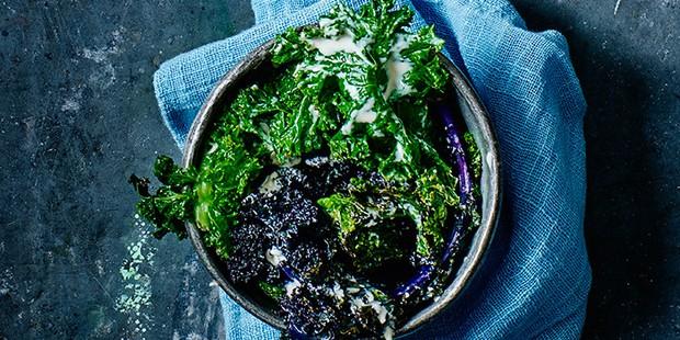 Kale salad with tahini and lemon dressing in a dark bowl
