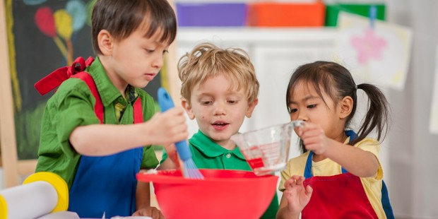 Three children in colourful aprons making crafts