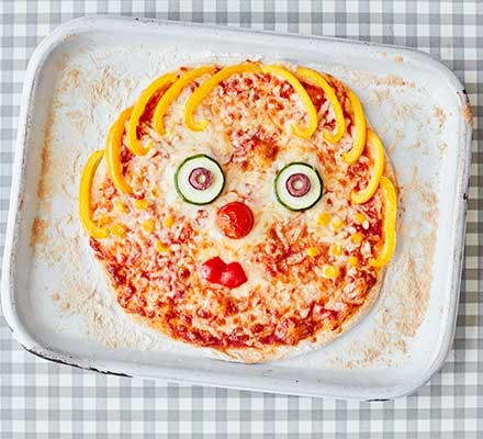 A baking tray with a pizza on it that has a face made with vegetables