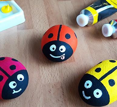 Three painted rock ladybirds