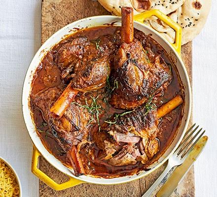 A casserole dish serving lamb shank Madras