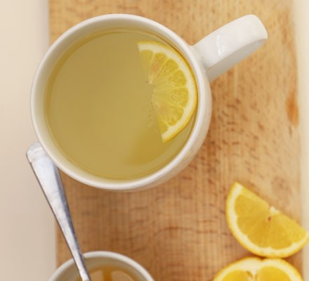 Mug with honey & lemon tea and lemon slices