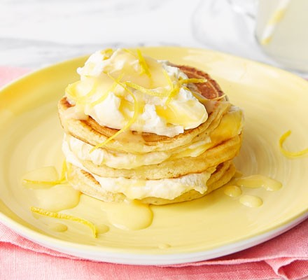 Pancakes with cream, lemon curd and zest on plate