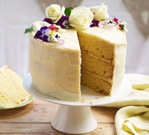 Lemon and elderflower celebration cake topped with flowers