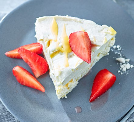 Slice of lemon meringue parfait on a plate topped with strawberries