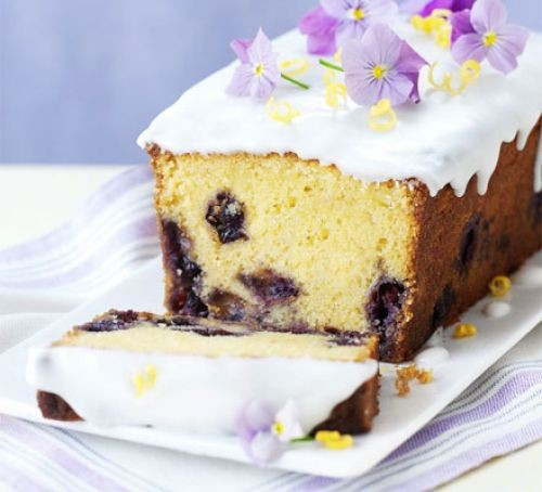 Lemon and blueberry loaf cake topped with icing and flowers