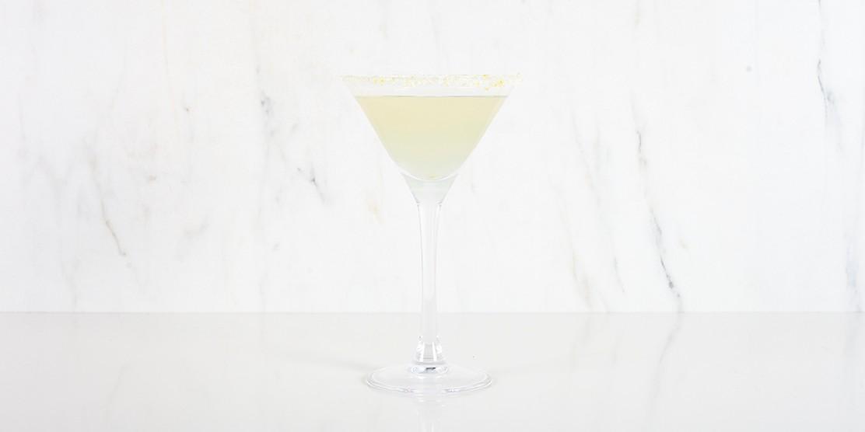 Lemon drop cocktail in hoog martiniglas op marmeren achtergrond