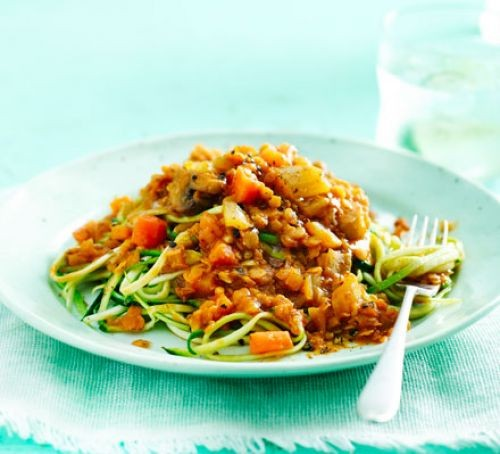 Courgetti topped with lentil ragu, served on a plate with a fork