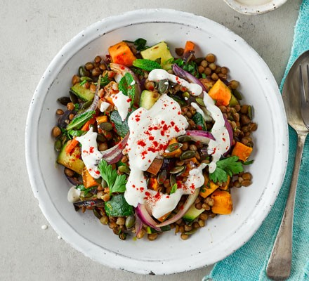 A bowl of lentil salad with tahini dressing