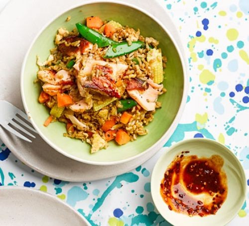 Fried rice with salmon and sauce in bowls