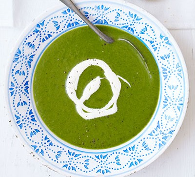 Green soup in white and blue bowl